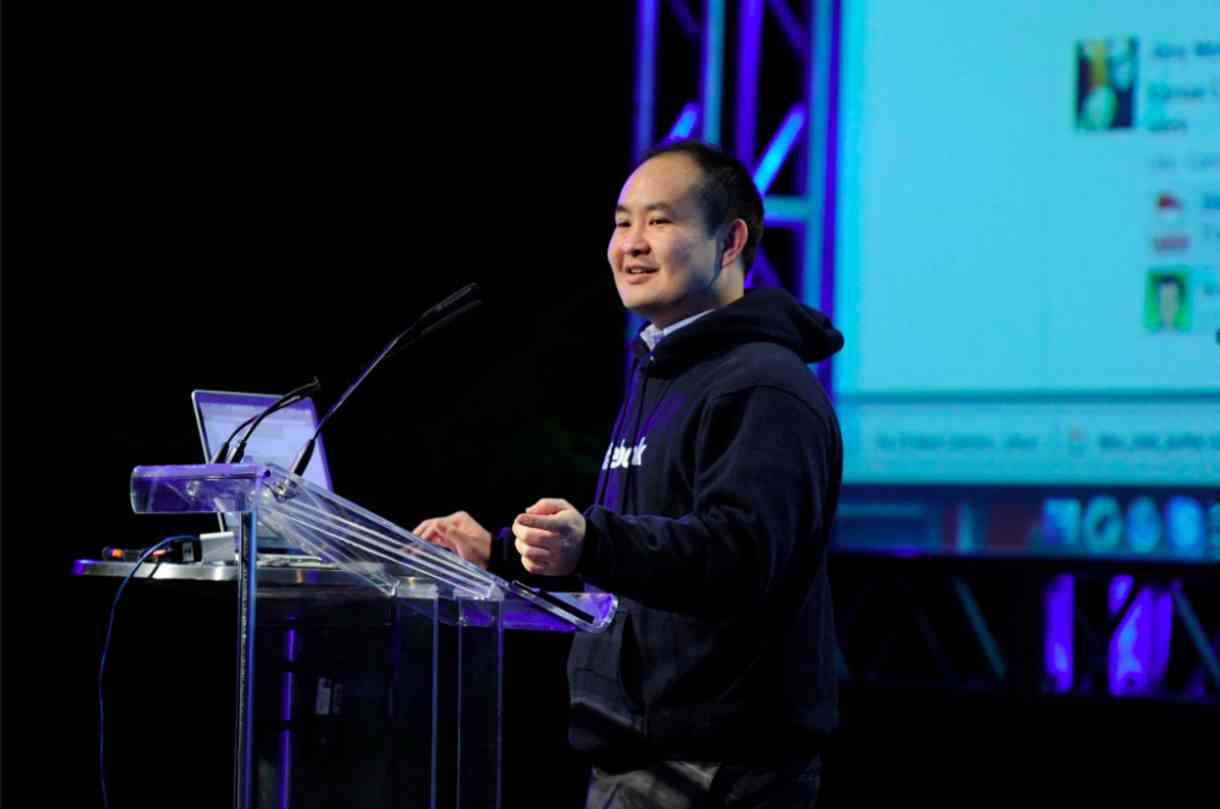 Dennis Yu stands at a podium giving a presentation.