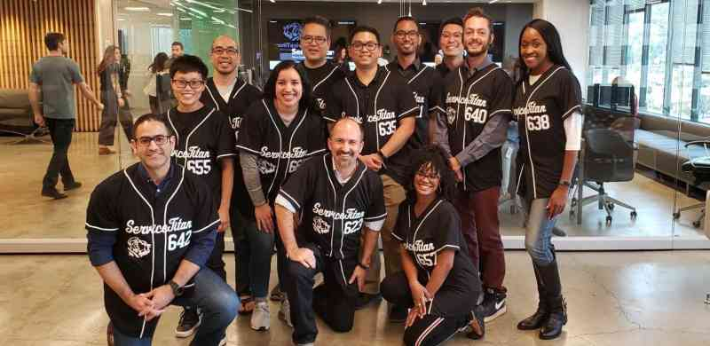 12 members of the ServiceTitan team wearing matching baseball jerseys smile at the camera.