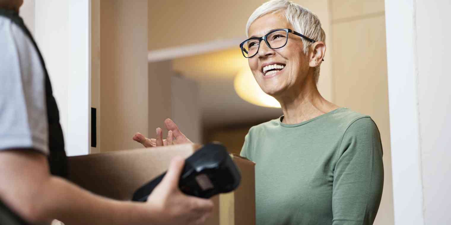 A senior woman accepts a package from a delivery person who is holding a scanning or payment device.