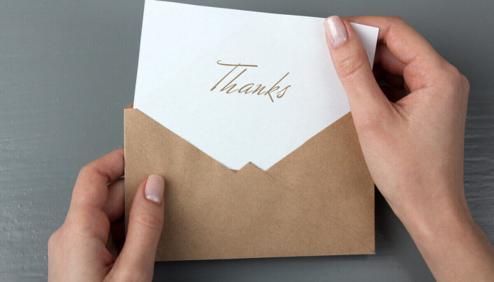 Someone opening a thank-you note