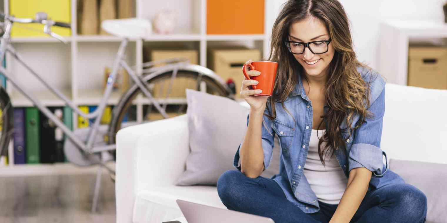 A smiling woman sits at home with a mug and a laptop.