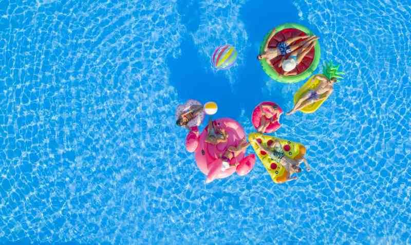 Aerial view of a pool on a sunny day. People float on pool inflatables shaped like a flamingo, donut, pizza, pineapple, and watermelon.