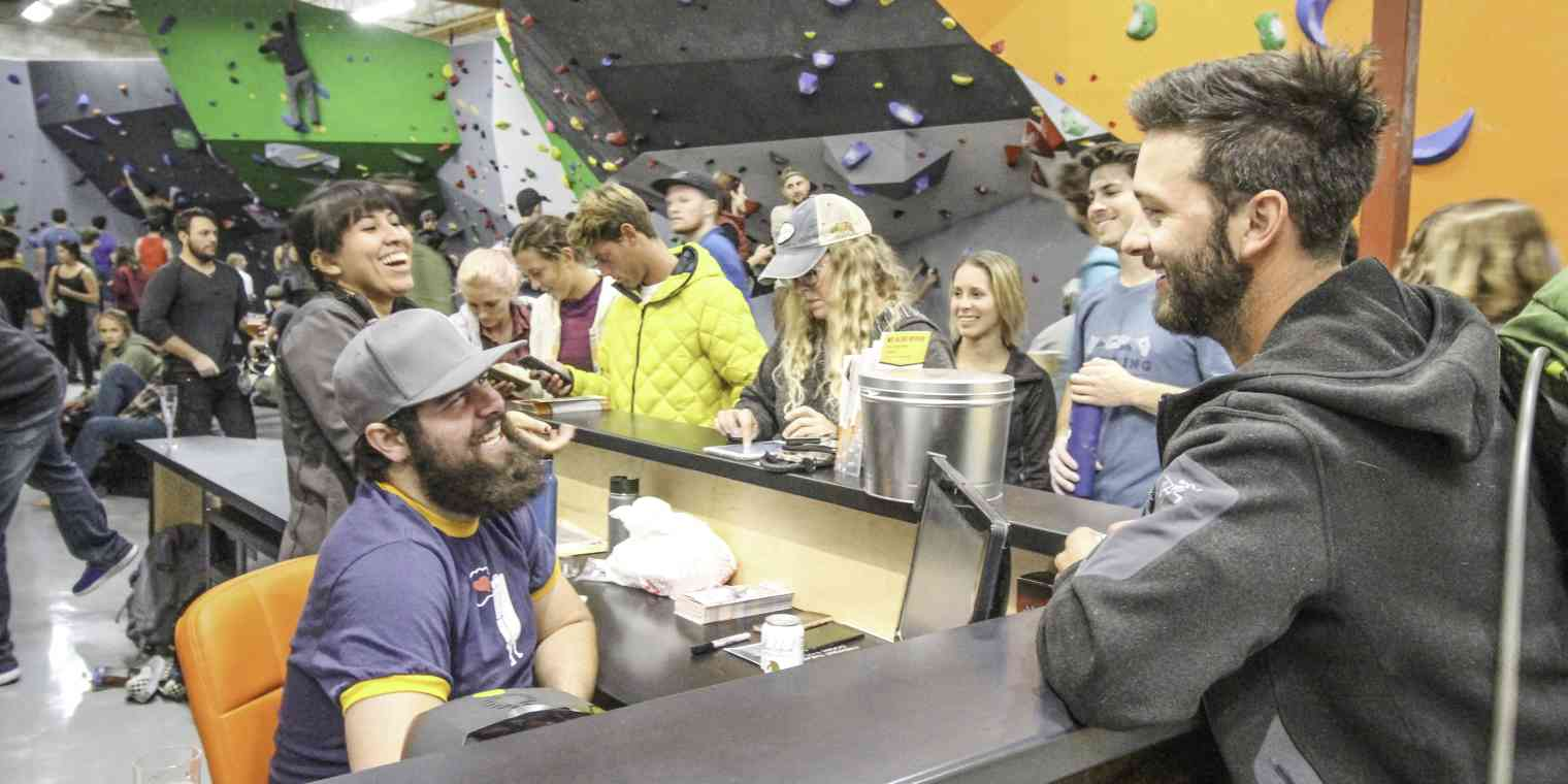 A group of people smiling and laughing at an indoor climbing gym.