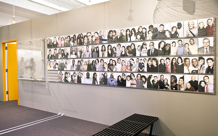 A wall in the StoryCorps office with about 50 photos of people.
