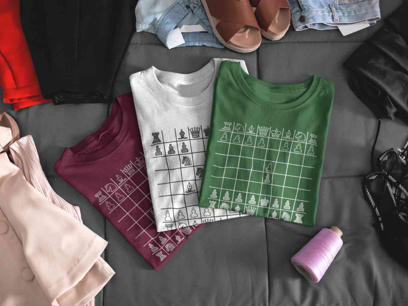 Three folded T-shirts with chess boards printed on the front.