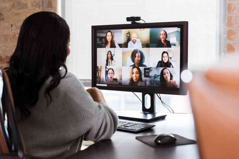 A woman sits at a desk looking at a screen showing nine participants in a video call.