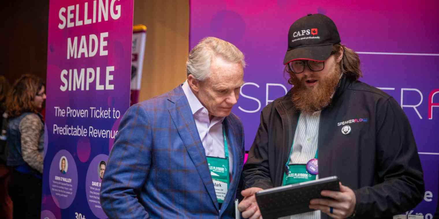 """Two men stand in front of signage at a conference. One of them holds a tablet. The sign behind them reads """"Selling made simple."""""""