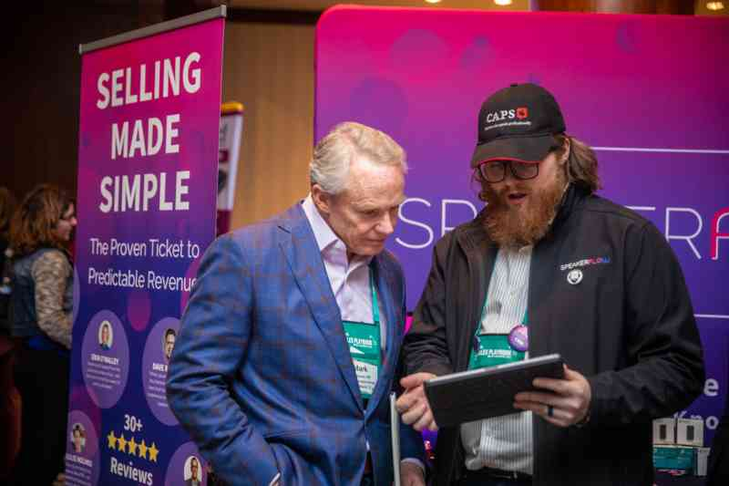 "Two men stand in front of signage at a conference. One of them holds a tablet. The sign behind them reads ""Selling made simple."""