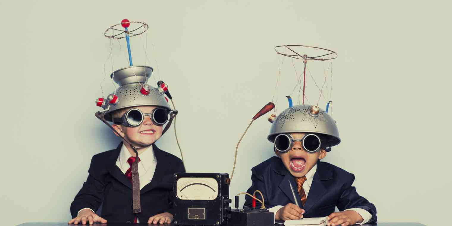 Two grinning children sit at a table wearing goggles with colanders on their heads.