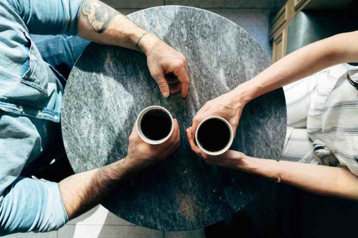 Two sets of hands across a table from each other holding cups of coffee