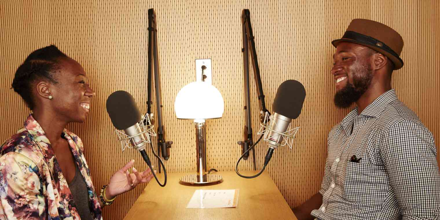 An interview with a woman and a man sitting at a desk with microphones.