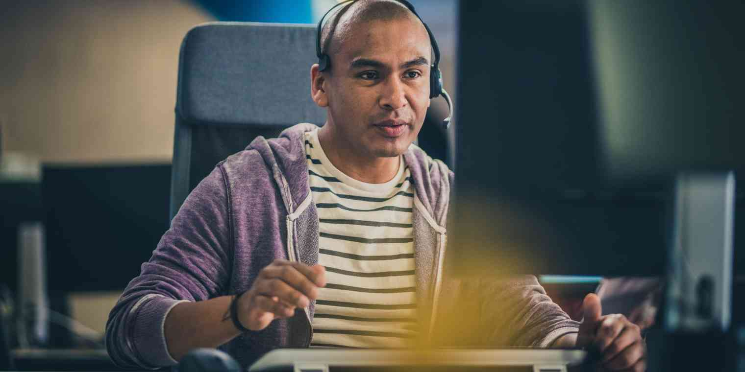 A man wears a headset and sits in front of a computer.