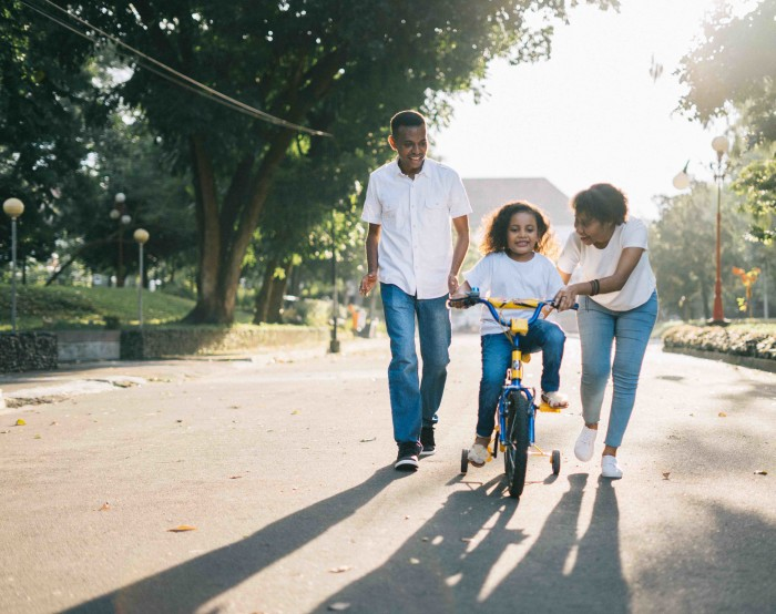 Image of child learning to ride a bike with the help of adults