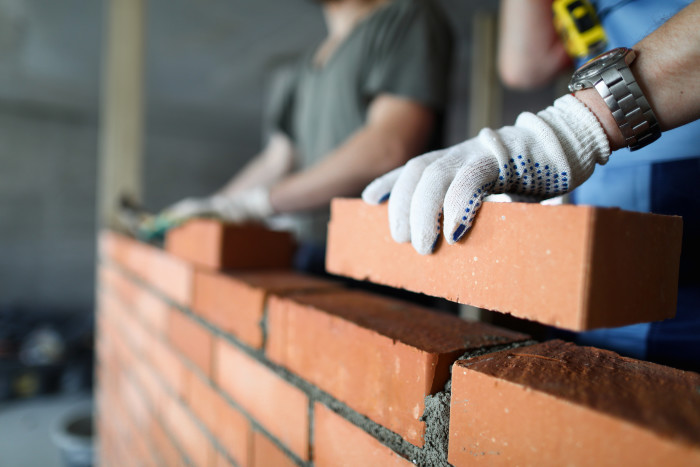 A brick wall being laid. The image shows a worker's hand in the foreground holding a brick above the in-progress wall.