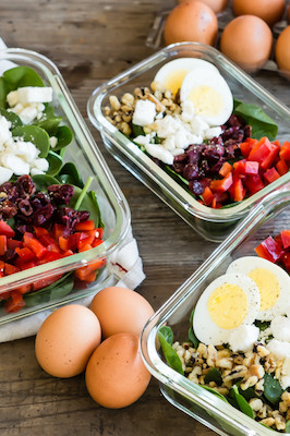 A healthy and nutritious salad featuring organic hard-boiled eggs, fresh spinach, walnuts, feta cheese, red bell pepper, and cranberries. Portioned out in meal prep containers and served with an orange zest vinaigrette. | peteandgerrys.com