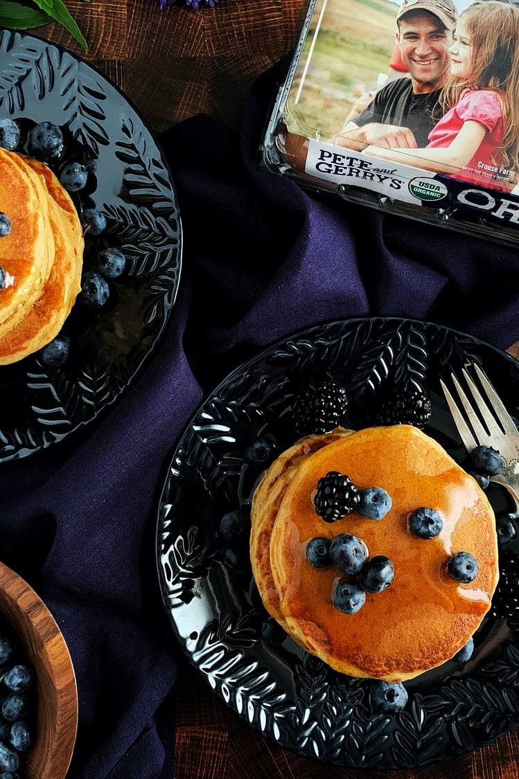 Whole wheat protein pancakes topped with blueberries and maple syrup, alongside the carton of Pete and Gerry's Organic Eggs used to make them.