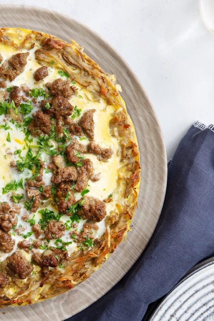 This potato quiche is cooked with an organic egg filling until golden brown. Pictured on top of the quiche are crumbled ground beef, shredded cheese, and parsley. | peteandgerrys.com