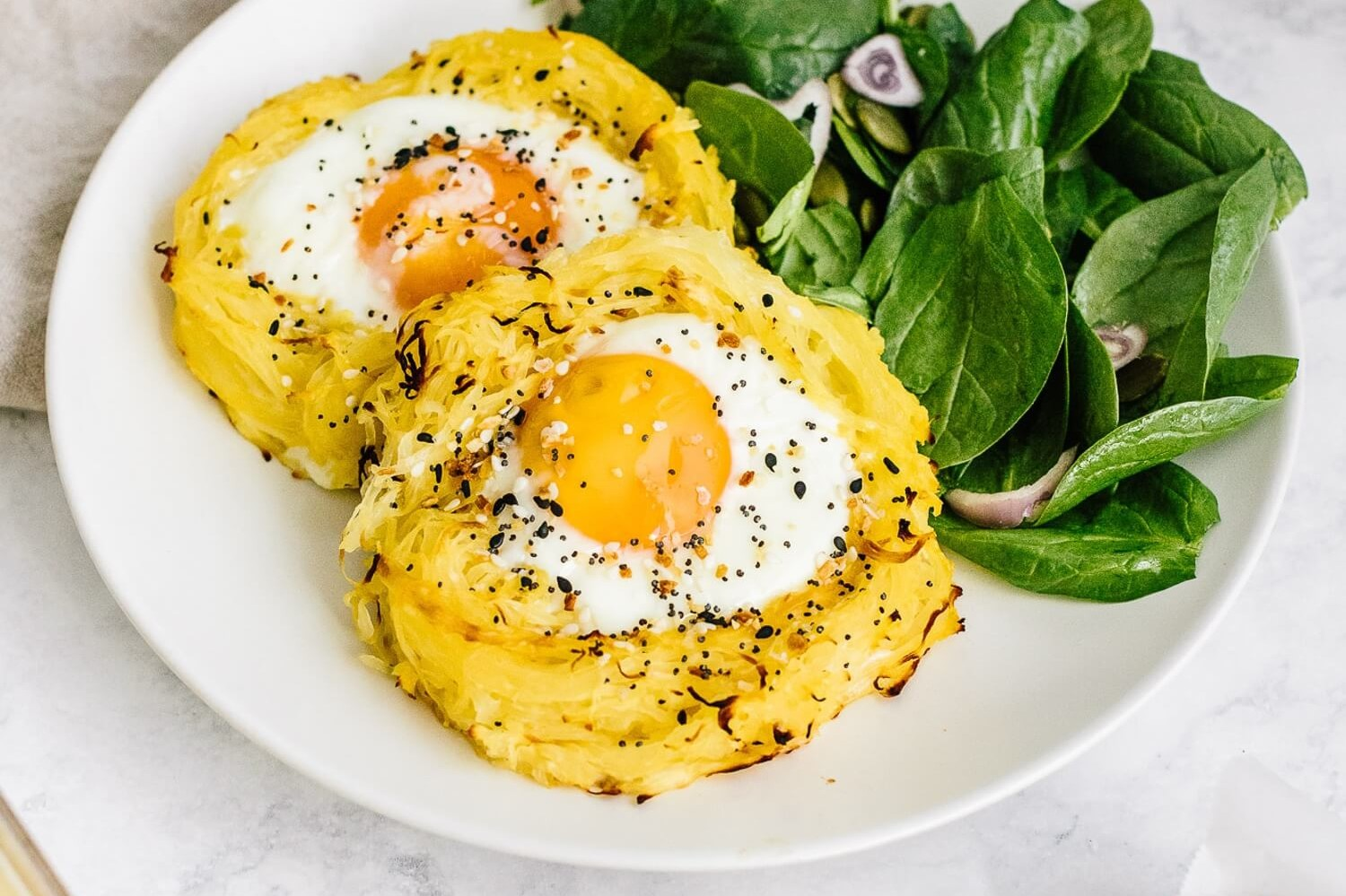 This picture features spaghetti squash shaped like a bird's nest. In the middle of the nest is a sunnyside up organic egg. Enjoy with mixed green and fresh black pepper. | peteandgerrys.com