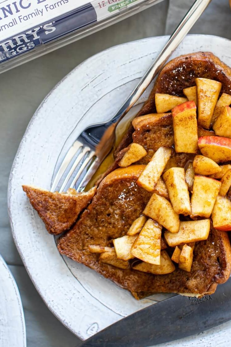 This cinnamon apple French toast is drenched in a custardy combination of egg, sugar, and cinnamon, then pan fried until golden brown and finished with chopped apple and maple syrup. | peteandgerrys.com