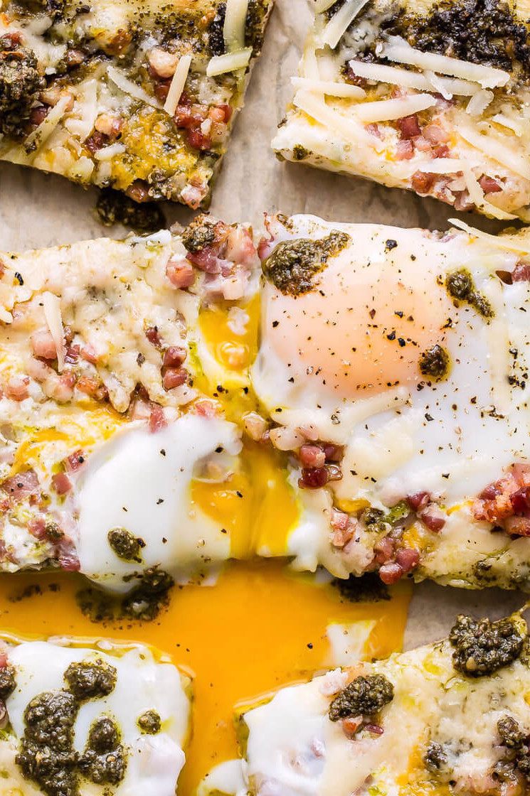 The pancetta egg flatbread features crispy and delicious pancetta, green pesto, and runny fried organic eggs. | peteandgerrys.com