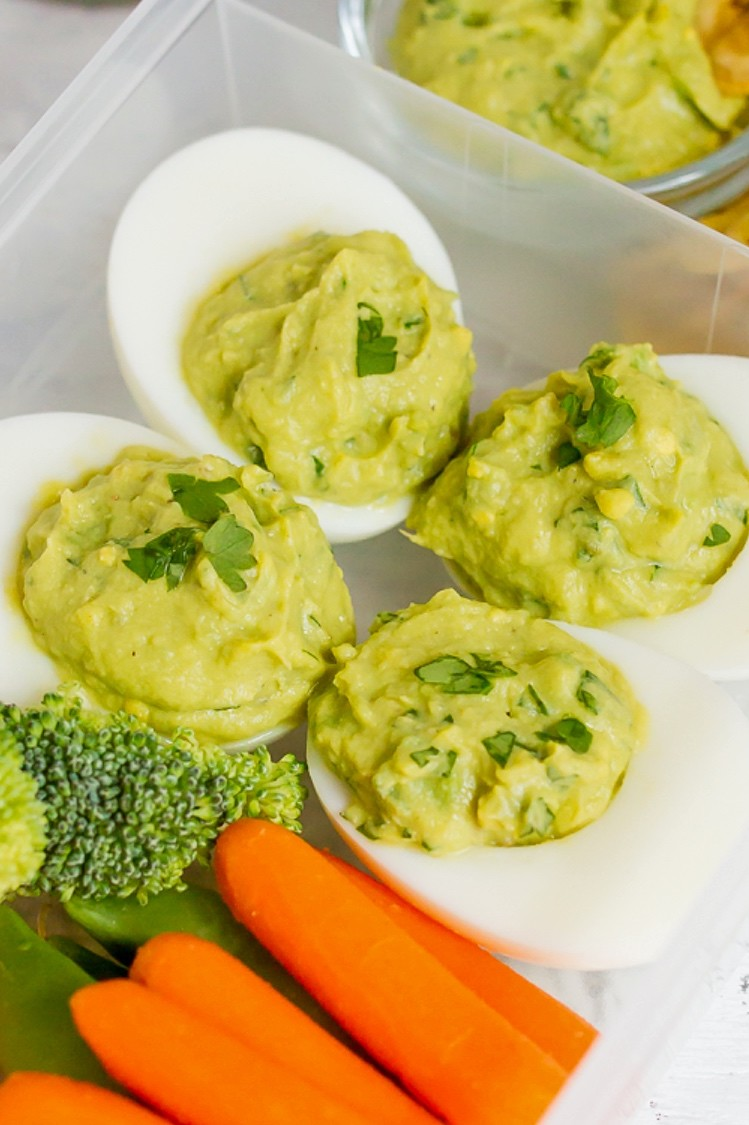 Avocado deviled eggs in a meal prep container. Each hard-boiled egg half features a guacamole inspired filling. Served alongside fresh vegetables and homemade plantain chips. | peteandgerrys.com