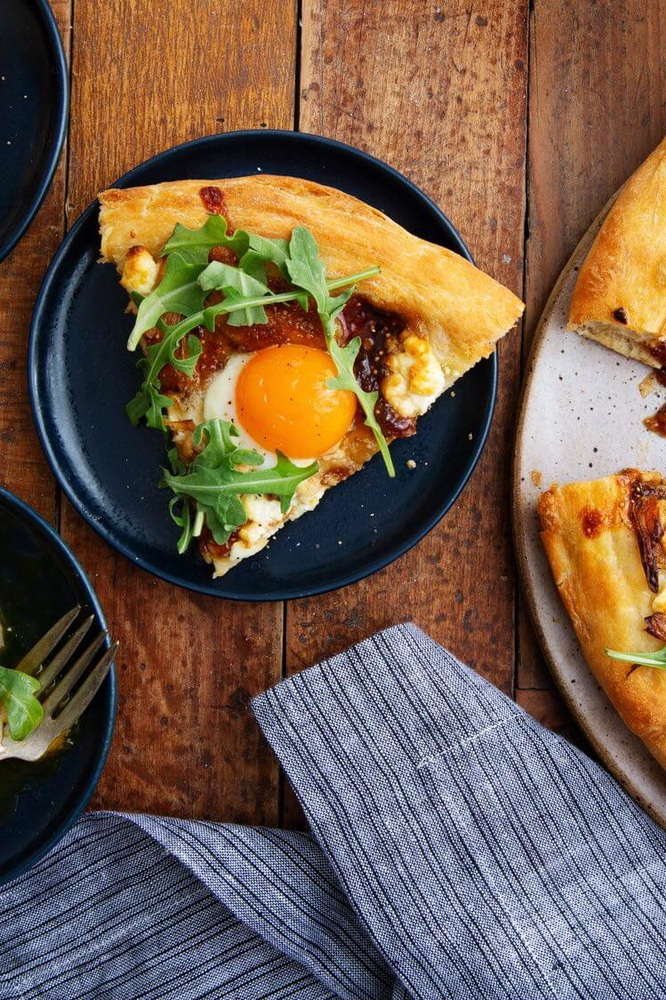 This good morning pizza features whole wheat dough, shallots, goat cheese, fig preserves, and arugula. Topped with a runny organic egg. | peteandgerrys.com