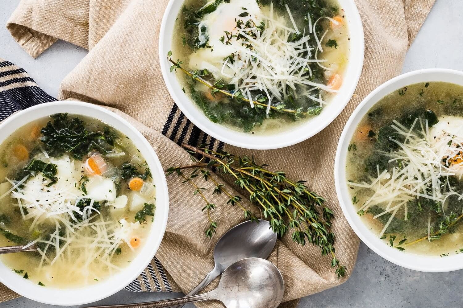 This winter kale and egg soup is perfect during the cold season and is vegetarian friendly. The soup is pictured with steamed kale, poached eggs, and parmesan cheese. | peteandgerrys.com