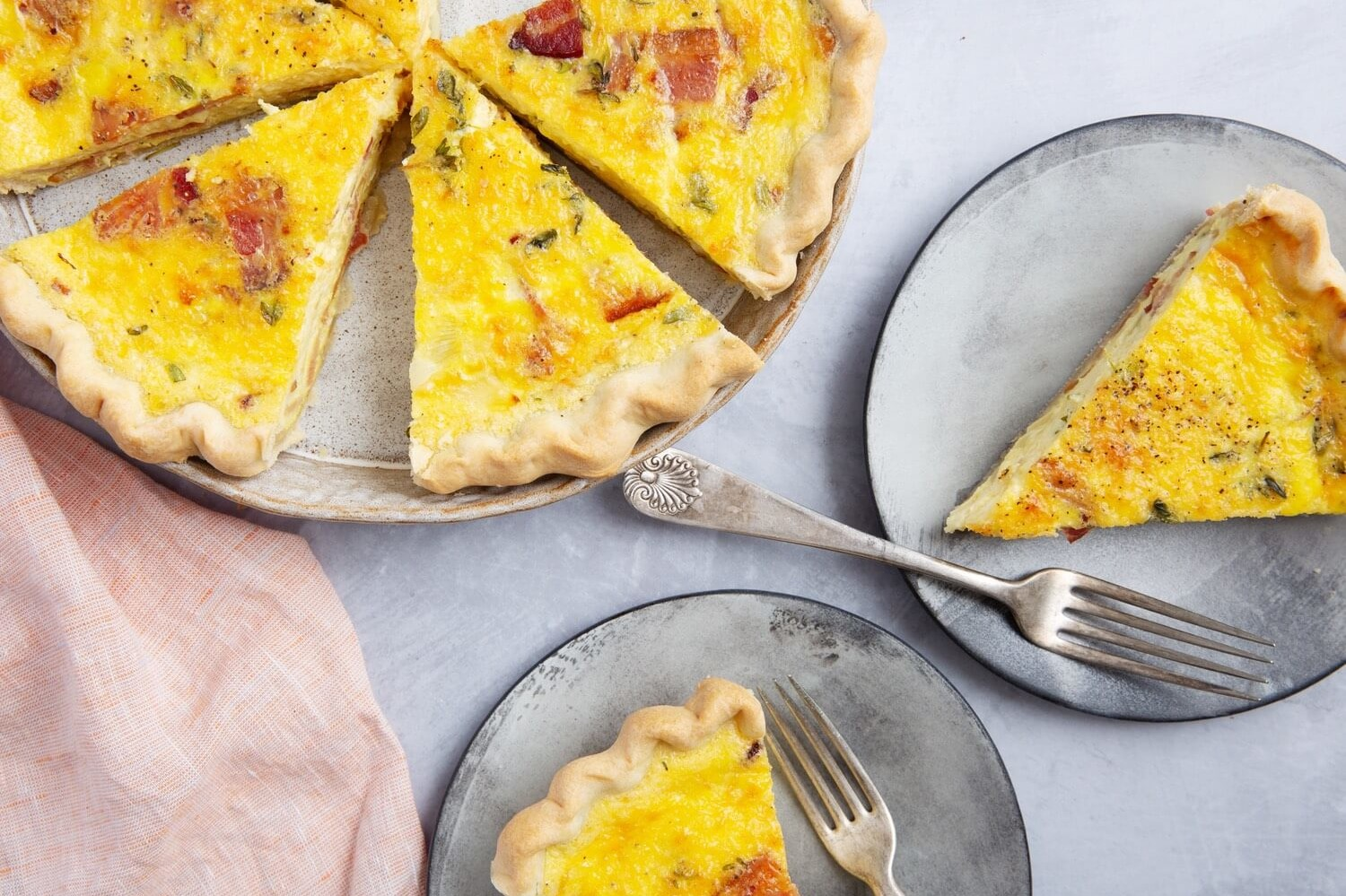 Pictured is a bright yellow swiss onion quiche with pieces of bacon and fresh thyme. This recipe features homemade crust and organic eggs. | peteandgerrys.com