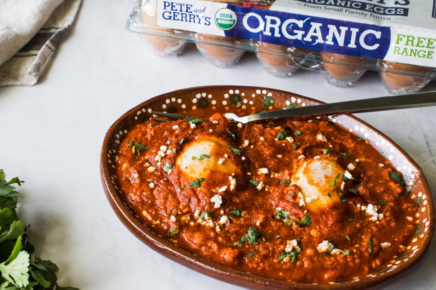 "Huevos ahogados (or ""drowned eggs""). Pete and Gerry's Organic Eggs gently poached in a smooth, smoky red salsa made from toasted guajillo chiles, chile de arbol, Roma tomatoes, and Mexican oregano."