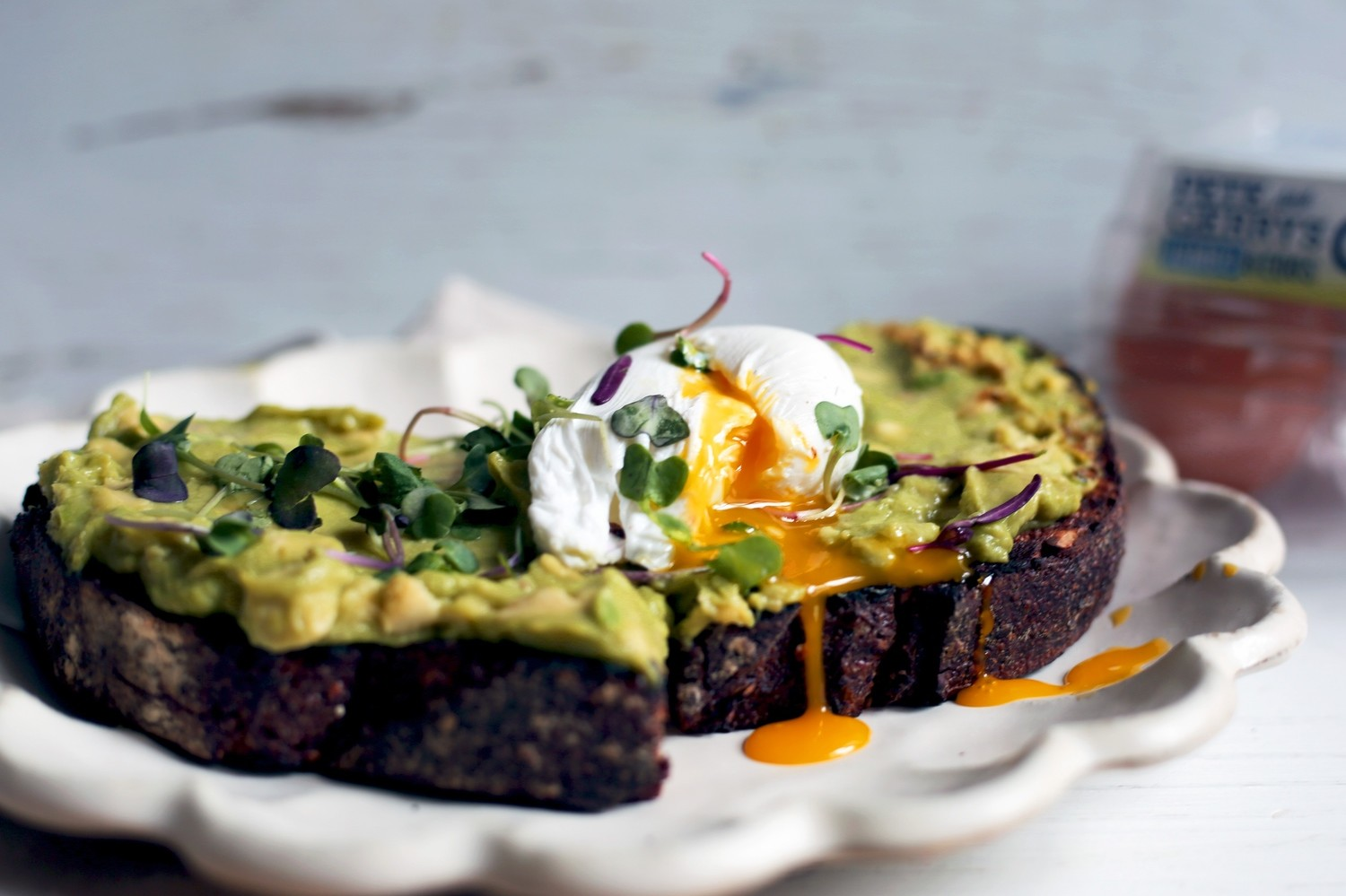Toasted slice of sourdough bread topped with mashed avocado, microgreens, a runny poached organic egg, and a drizzle of CBD-infused coconut oil. | peteandgerrys.com