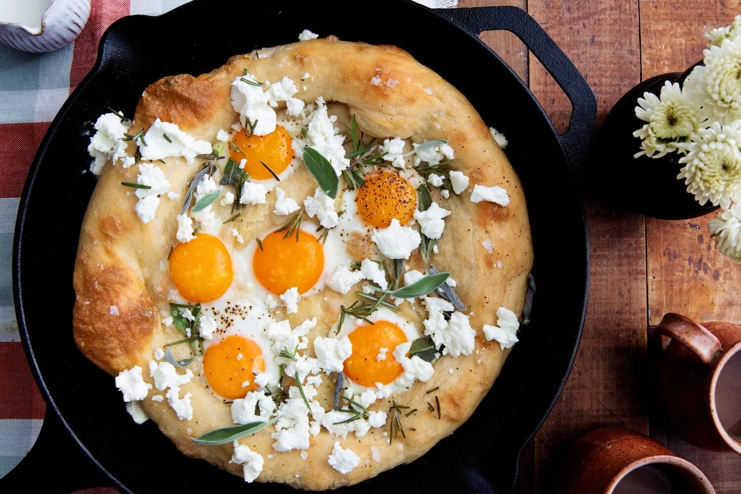 This sunny side up egg pizza features fluffy dough, topped with feta cheese, organic egg yolks, fresh sage, and rosemary. | peteandgerrys.com
