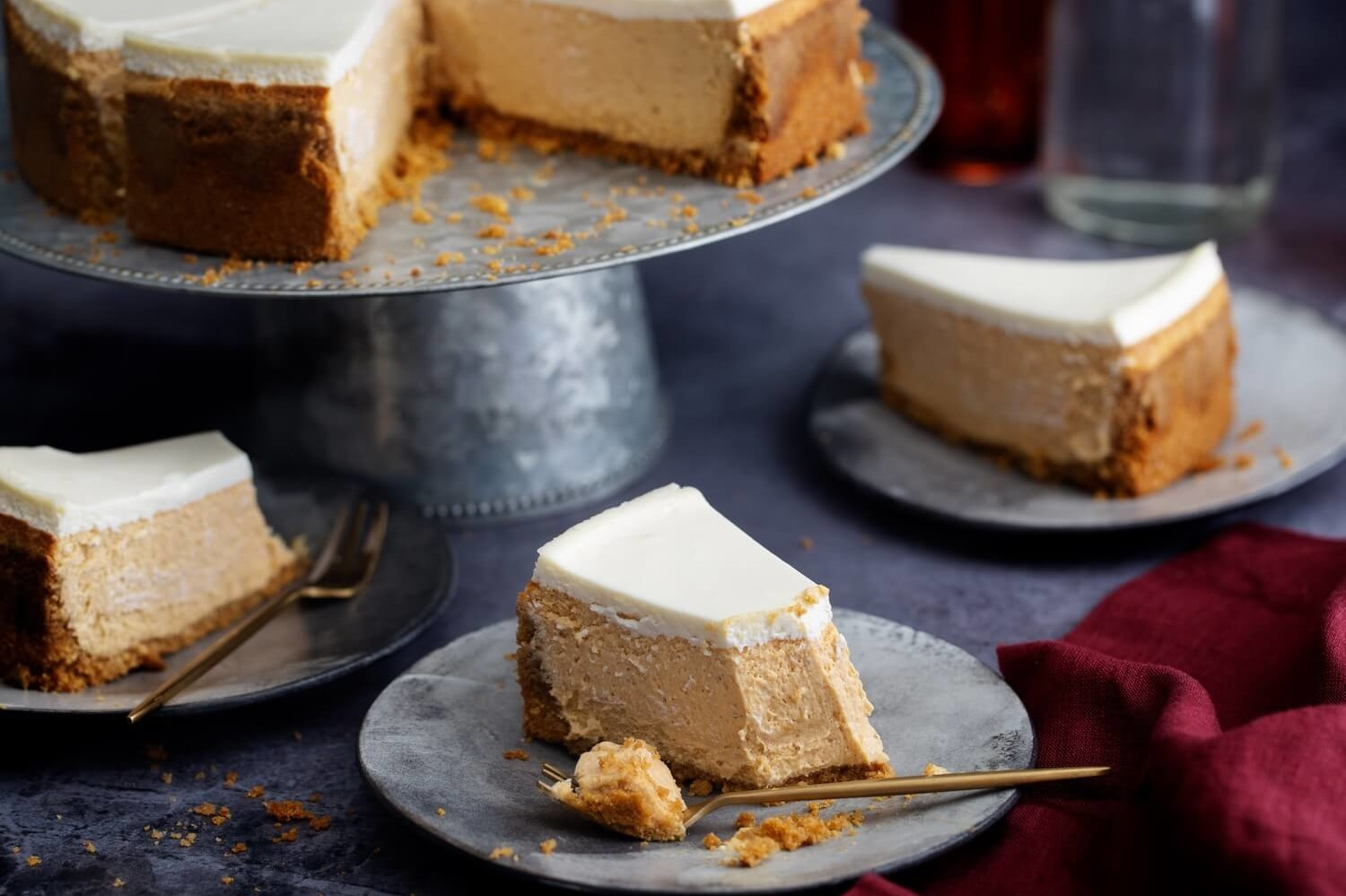 This maple pumpkin cheesecake starts with a cinnamon and ginger crust, then filled with a cream cheese, maple, pumpkin, bourbon mix. The cheesecake is topped with a bourbon, sour cream, spread. | peteandgerrys.com