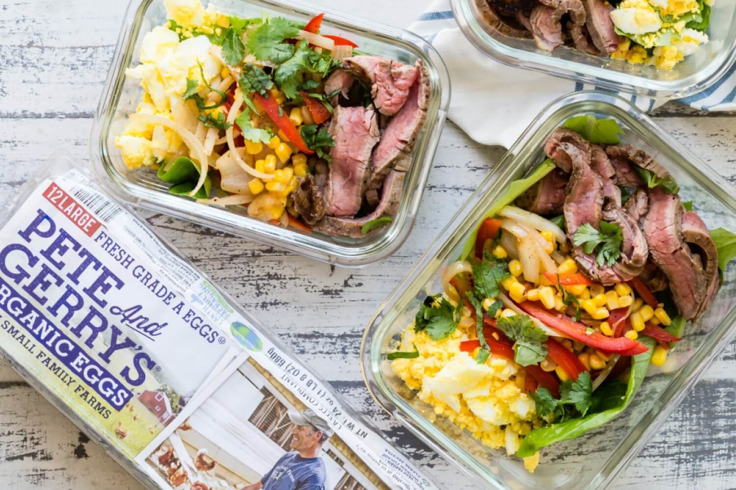 These low-carb fajita bowls are great for a make-ahead lunch or dinner. These bowls feature flank steak, bell peppers, cilantro, crumbled organic eggs, and sweet corn. | peteandgerrys.com
