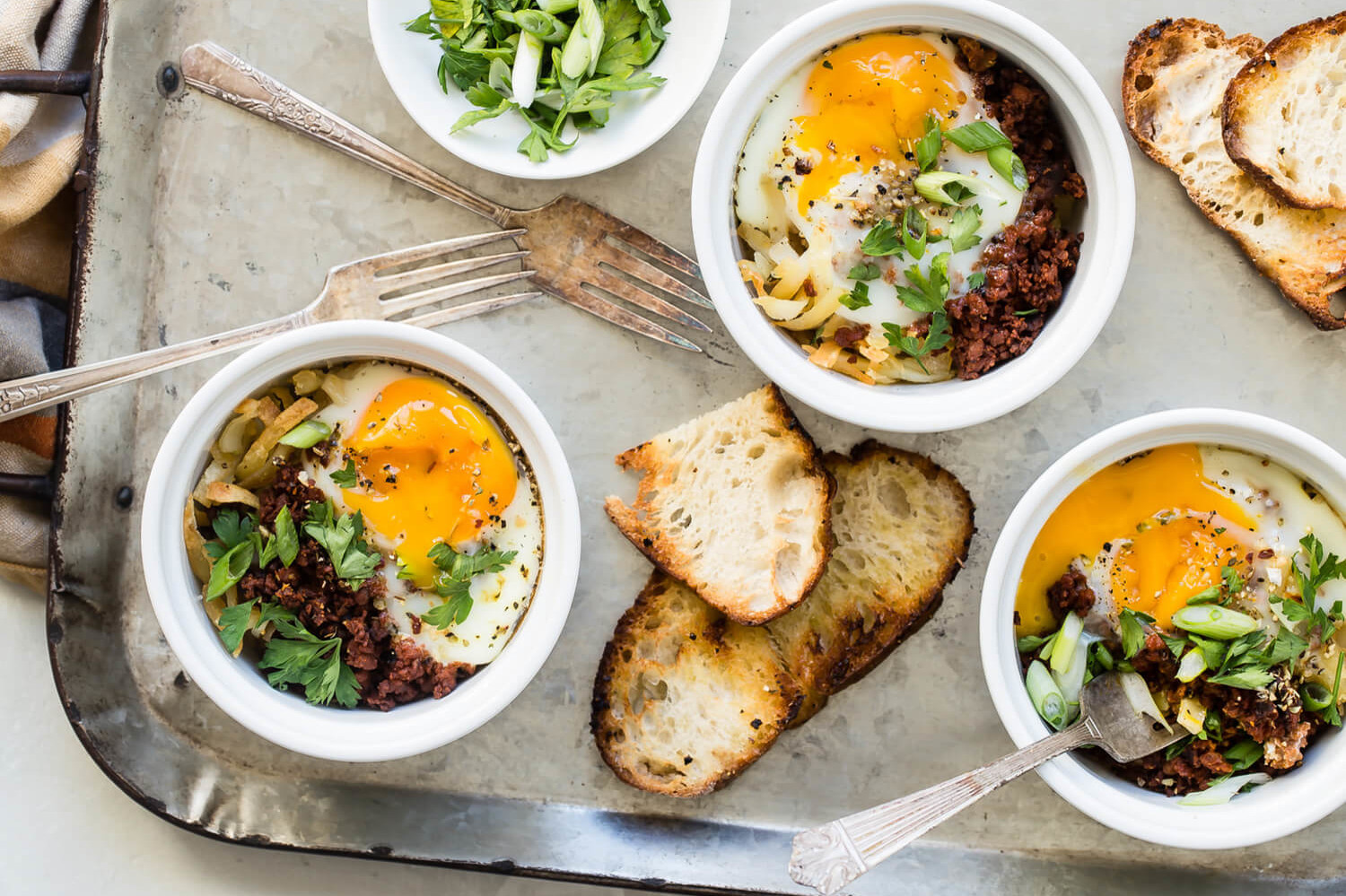 Organic eggs with runny yolks atop browned chorizo and hash browns. Each portion is baked in its own ramekin and served with toast on the side. | peteandgerrys.com