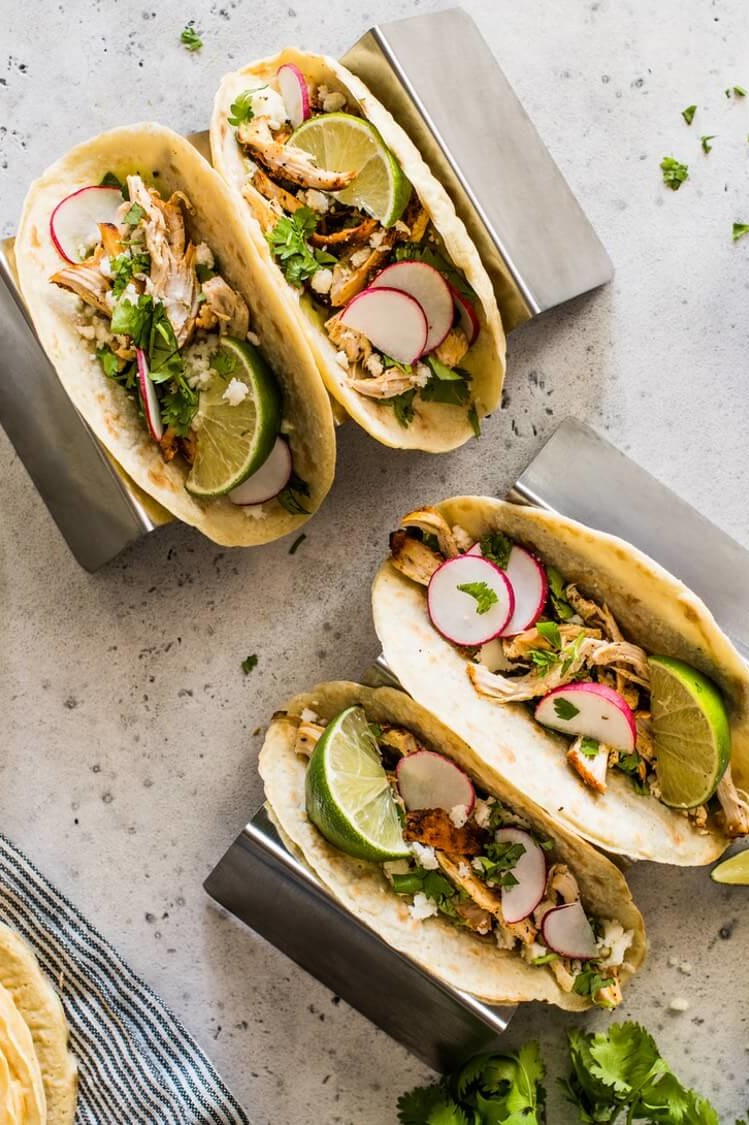These paleo chicken tacos feature homemade paleo tortillas made with tapioca flour. The filling is chicken thighs mixed with queso fresco, cilantro, thinly sliced radishes, and lime wedges. | peteandgerrys.com