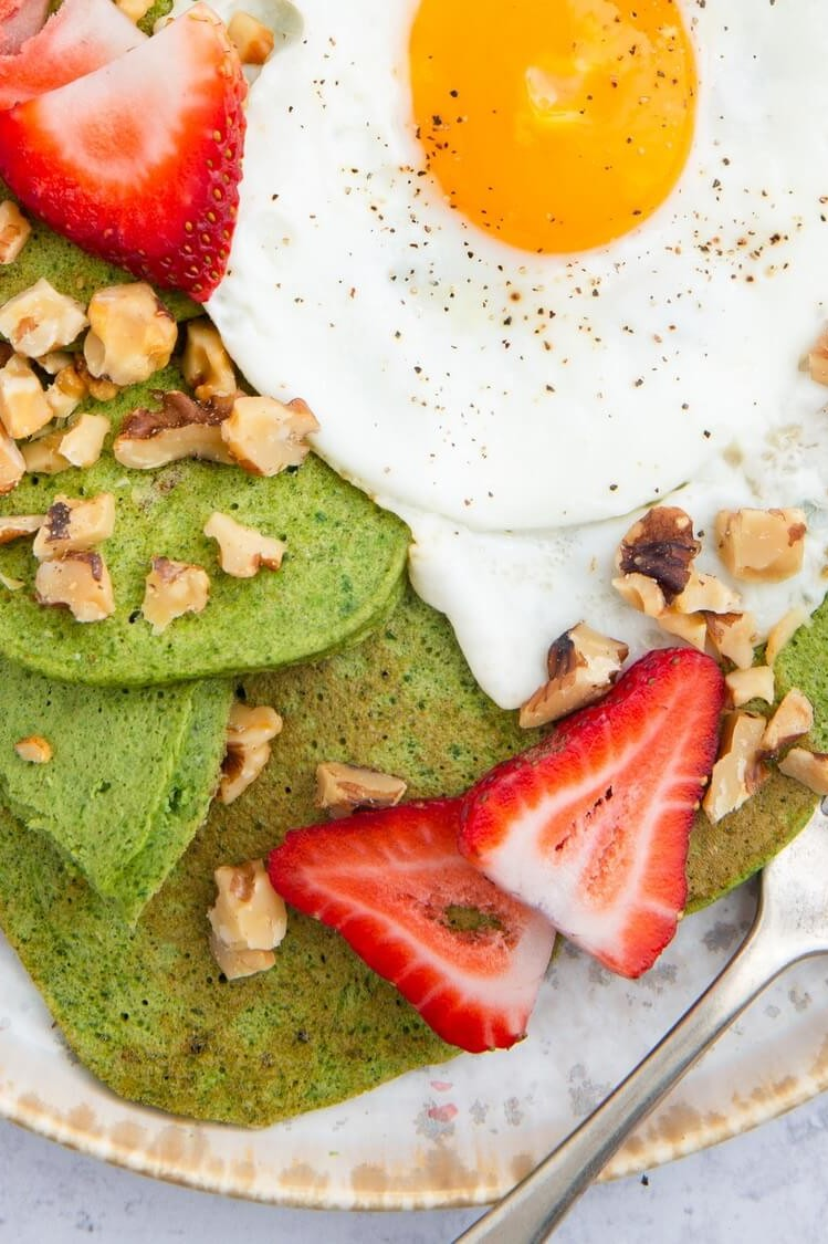 This green pancakes recipe features pancakes based with spinach and bananas. Our pancakes are topped with sliced strawberries, walnuts, and a fried egg. | peteandgerrys.com