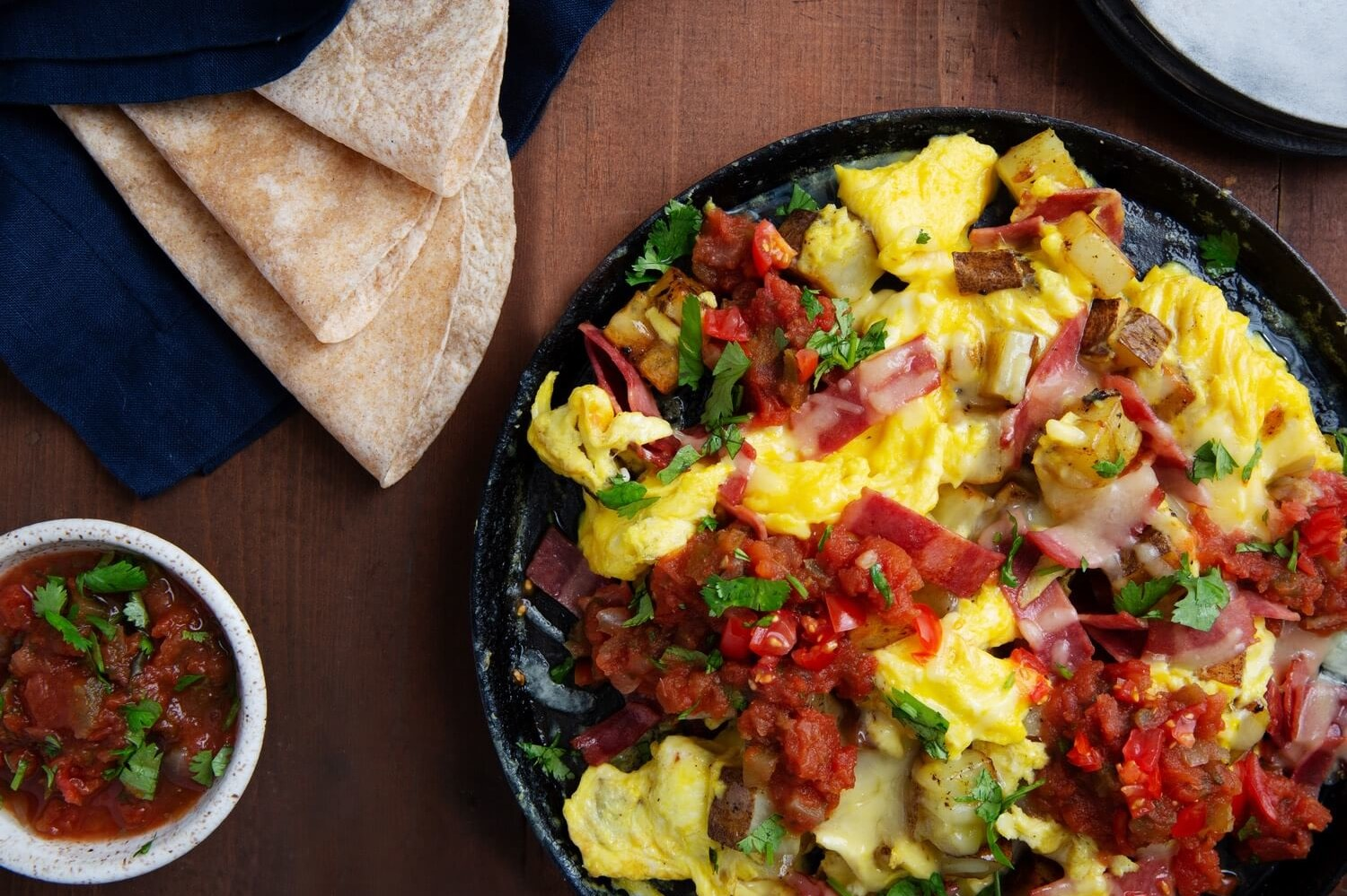 This one pan, texas style potato egg skillet is made with turkey bacon, russet potatoes, pico de gallo, smoked cheddar cheese, and soft tortillas. | peteandgerrys.com