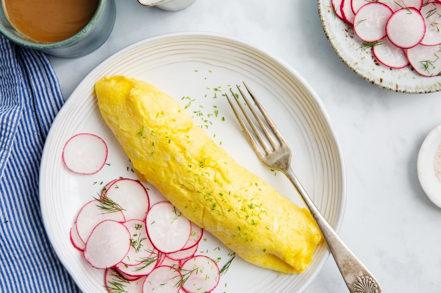A classic French omelette made with organic eggs and butter, boasting a golden yellow exterior and soft, custardy interior. The omelette is topped with minced chives and served with a side of thinly sliced radishes. | peteandgerrys.com