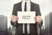 Businessman holding reit sign