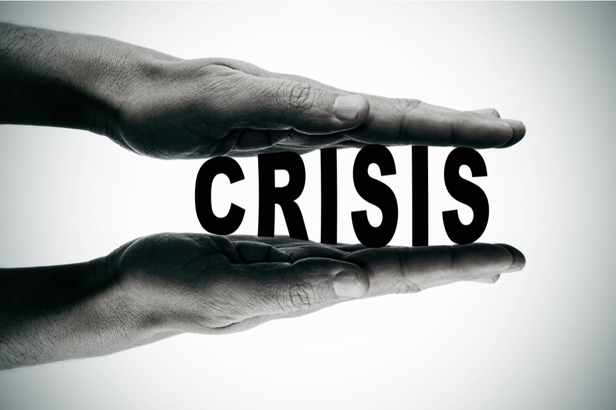 Man hands pressing the word crisis