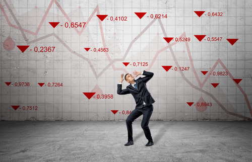 Frightened business man surrounded by red stock market indexes