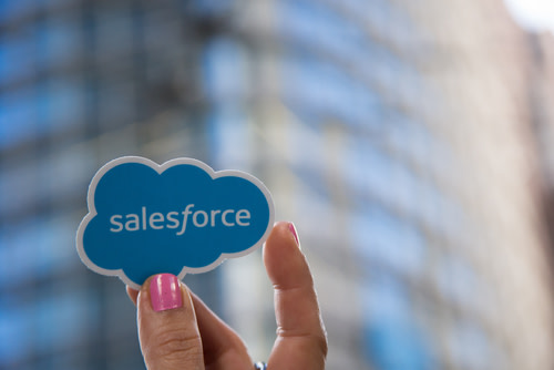 A hand holding up the Salesforce logo.