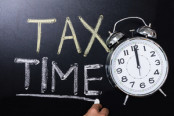 "Clock beside ""tax time"" written in chalk"