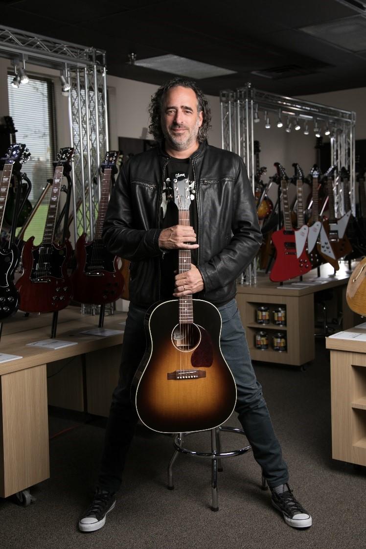James 'JC' Curleigh tenant un standard J-45 devant diverses guitares exposées, notamment des modèles Explorer, Firebird, Flying-V et SG.