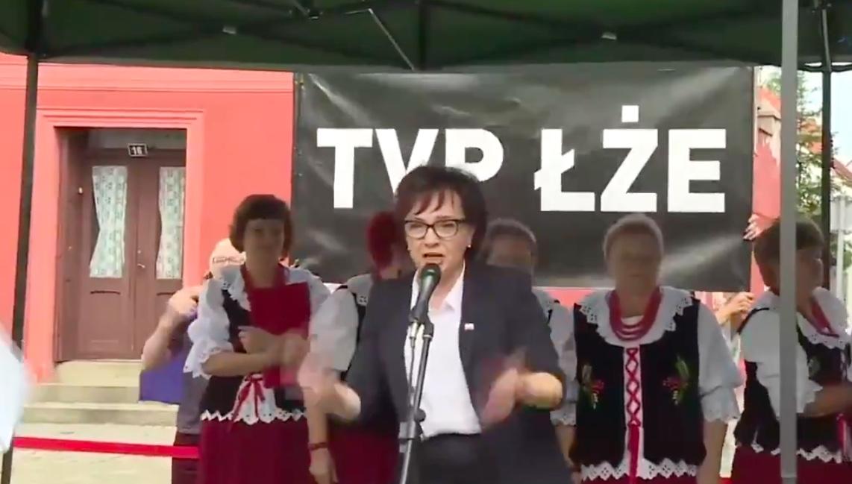 """Napis """"TVP ŁŻE"""" za plecami Elżbiety Witek w Otyniu"""