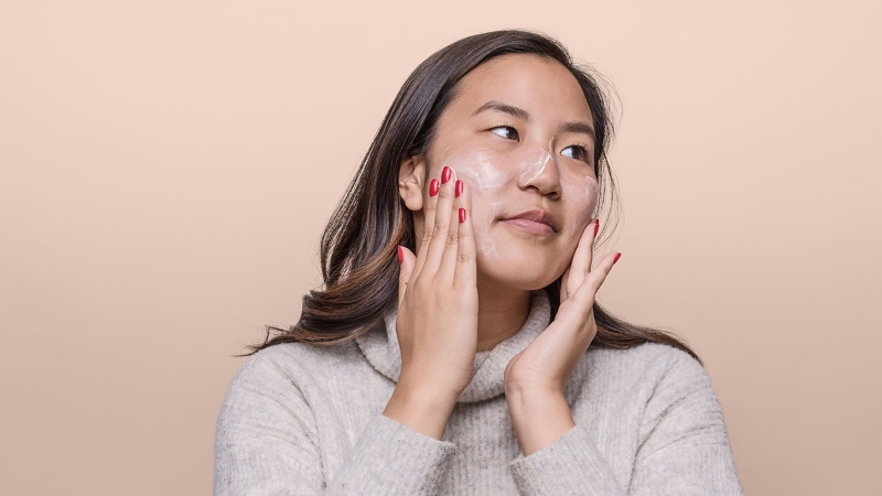 Woman adding skincare cream to her face