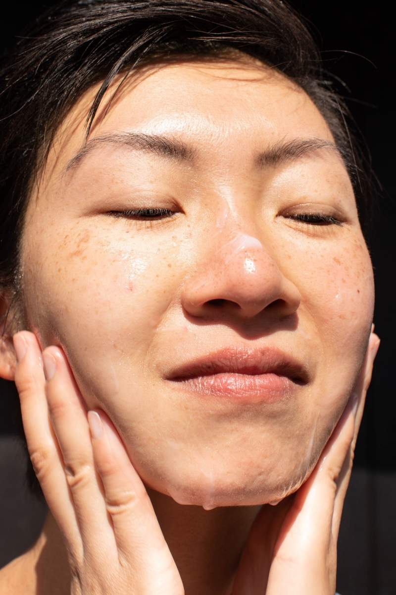 Closeup of person rubbing skincare cream on their face