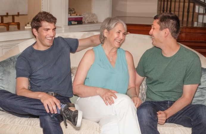 Family sitting on couch smiling (Nancy, David, and Glenn)