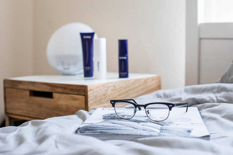 Glasses resting on bed with Curology set on nightstand in background