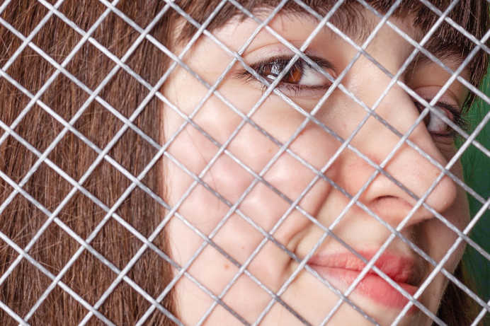 Closeup of a woman's face behind wire